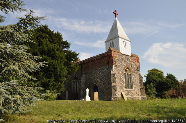 The unusual-looking church with squat wooden tower on top of the flint body of the church.