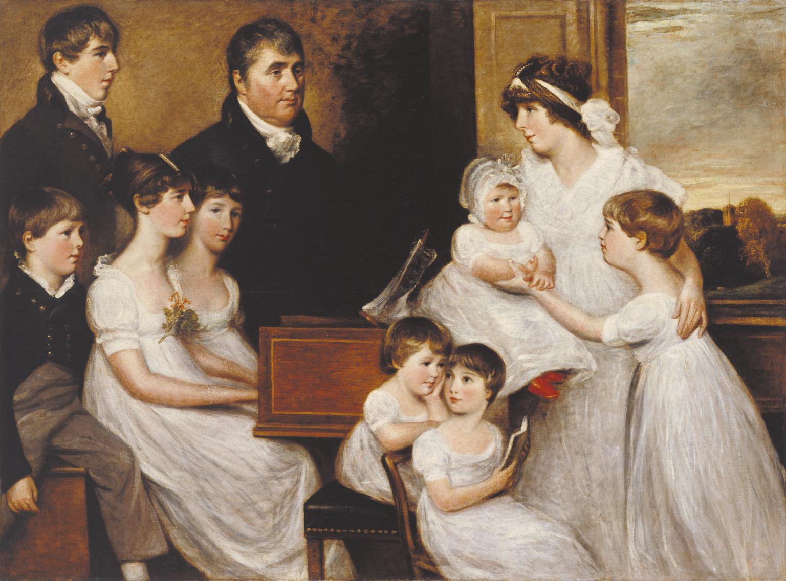 A family of eight stand around a piano. Through the window behind them, a church tower can just about be seen.