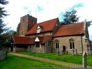 A photograph of St Peter's church, a small church made from flint, stone and brick.