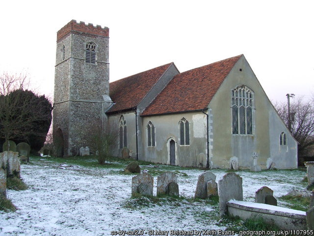 A photograph of the old church of St Mary's in Belstead, in the snow. Some stone headstones are in the foreground.