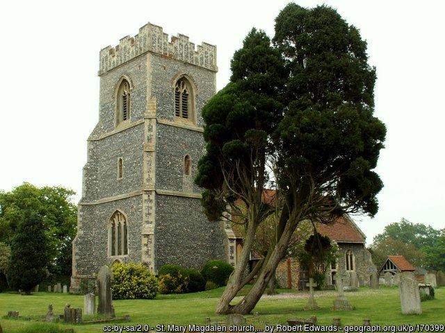 The church of St Mary Magdalene, taken by Robert Edwards. It has a flint tower and a red tiled roof. Some  stone headstones and a large old yew are in the foreground.